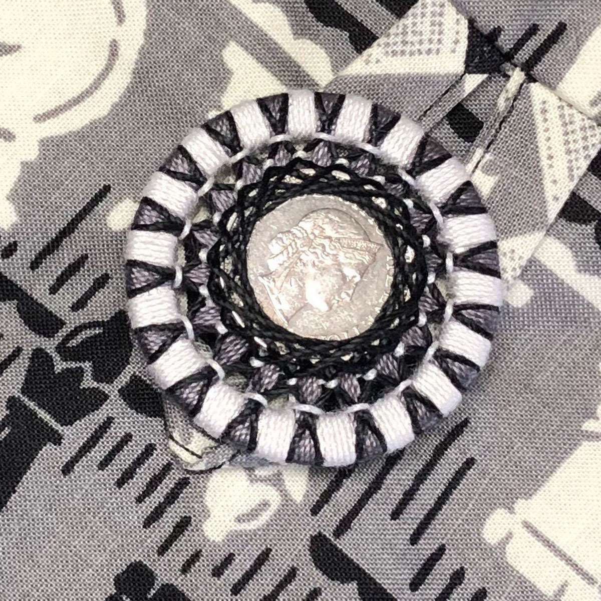 Zwirnknopf mit eingearbeiteter Münze
